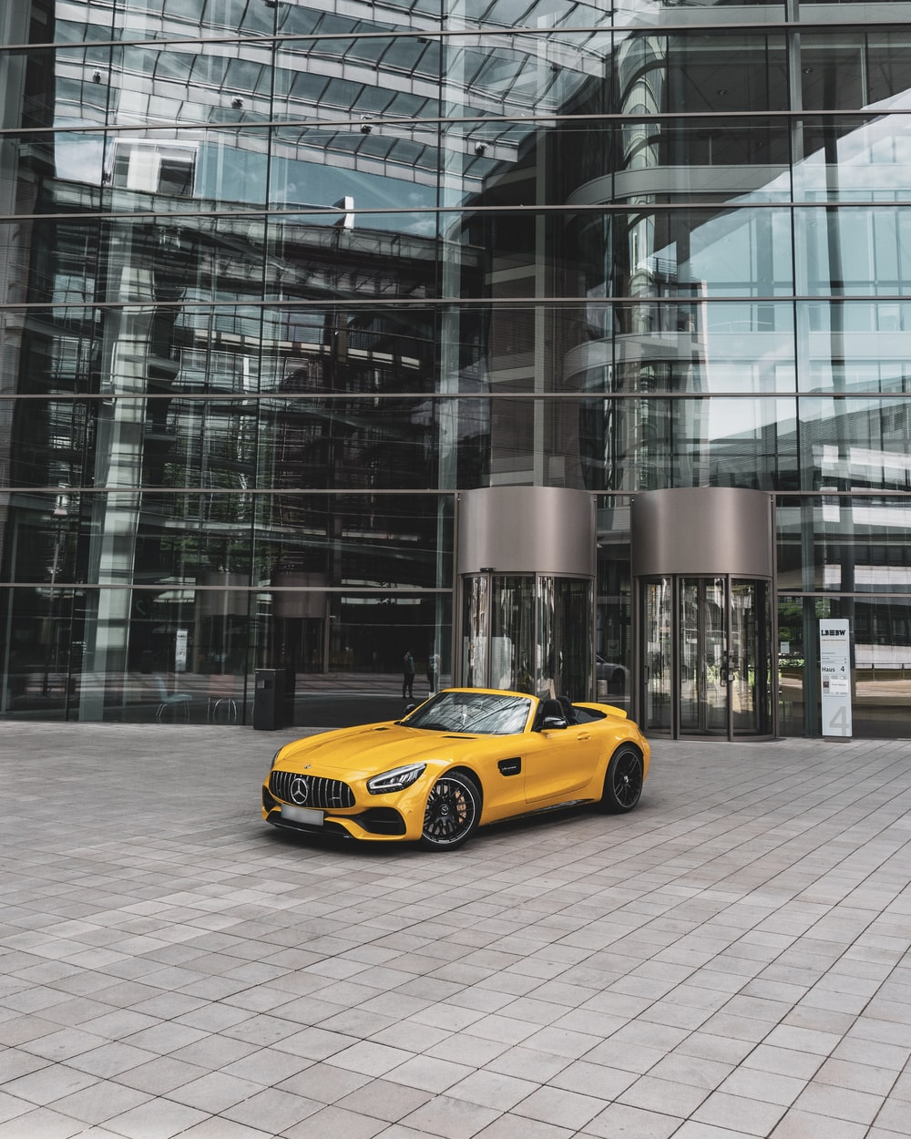yellow convertible coupe near building