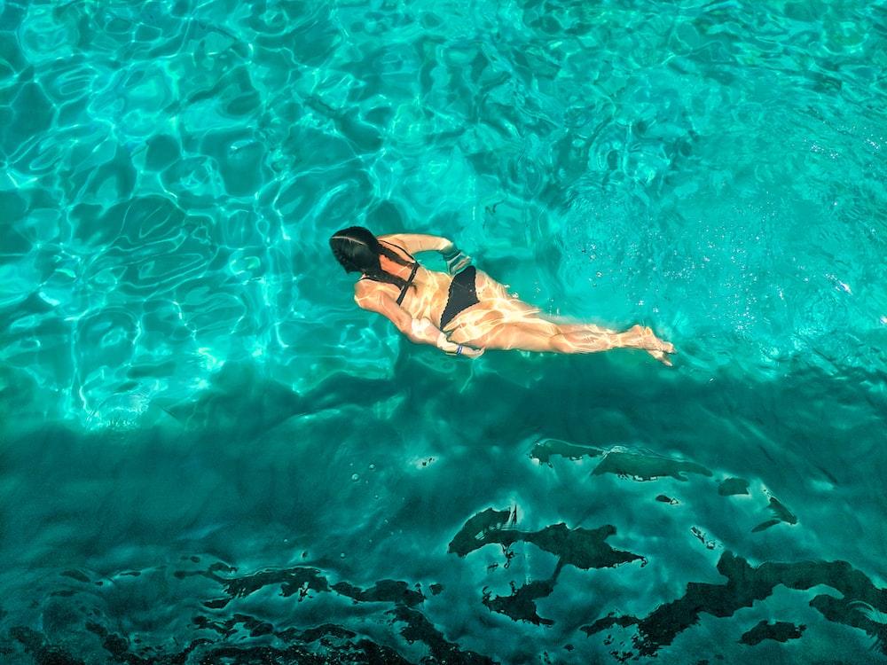 woman in black bikini swimming on clear blue water