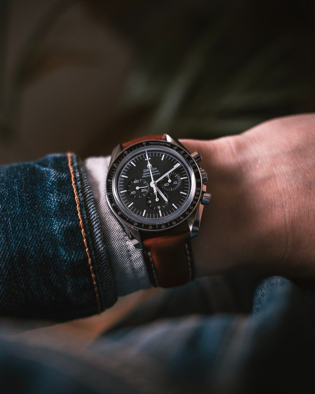 Wristshot of the Omega Speedmaster on a padded leather strap. Wearing a Levi's Trucker Denim Jacket and a grey oxford shirt.