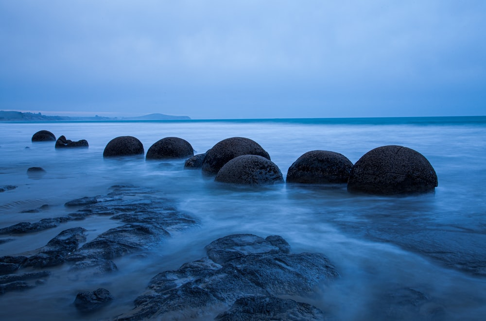 selective photography of rocks surrounded by body of water