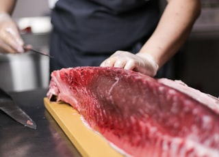 person cutting raw fish meat
