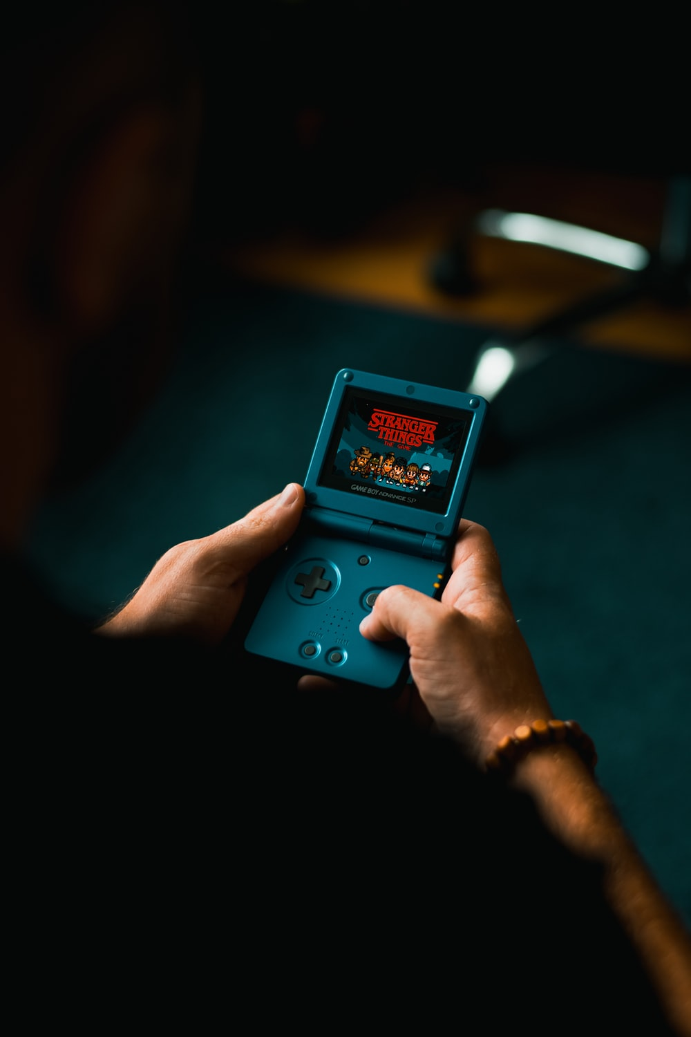 person playing blue Nintendo Advance SP