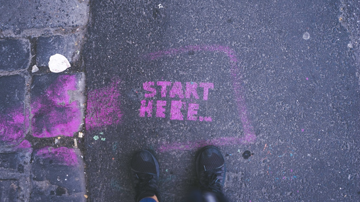 looking down at black shoes, the words START HERE... written in pink chalk on the asphalt