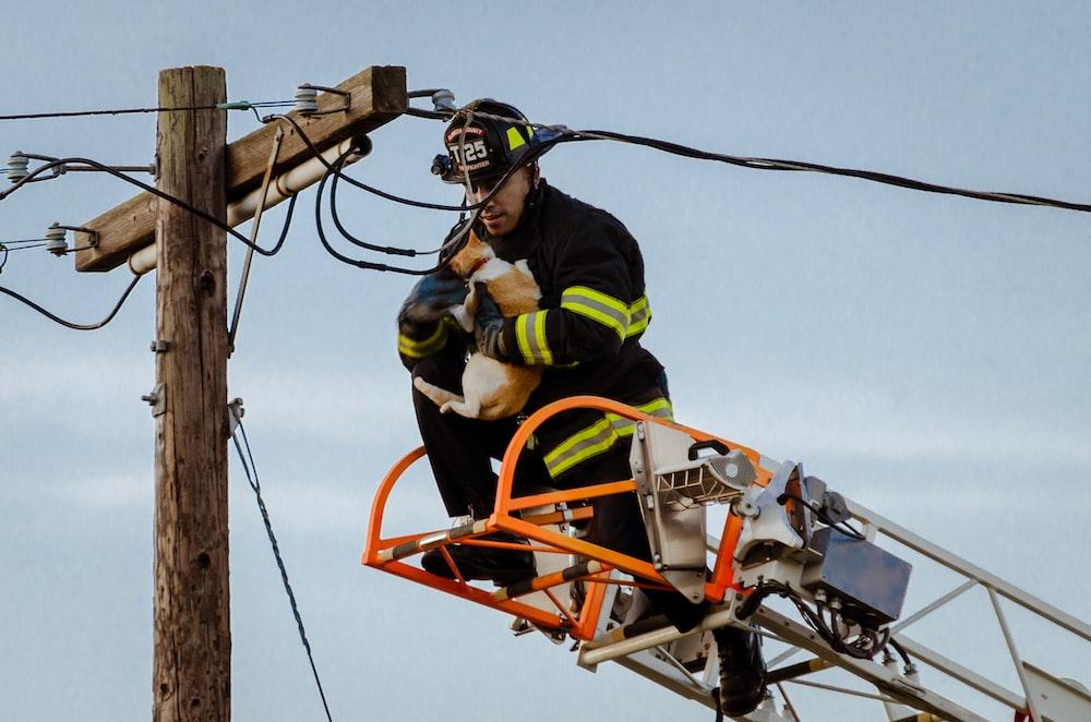 man saving car on utility post