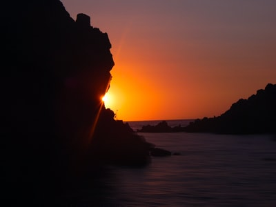 The sun peaking out of the rock as it sets on the Aegean sea.
