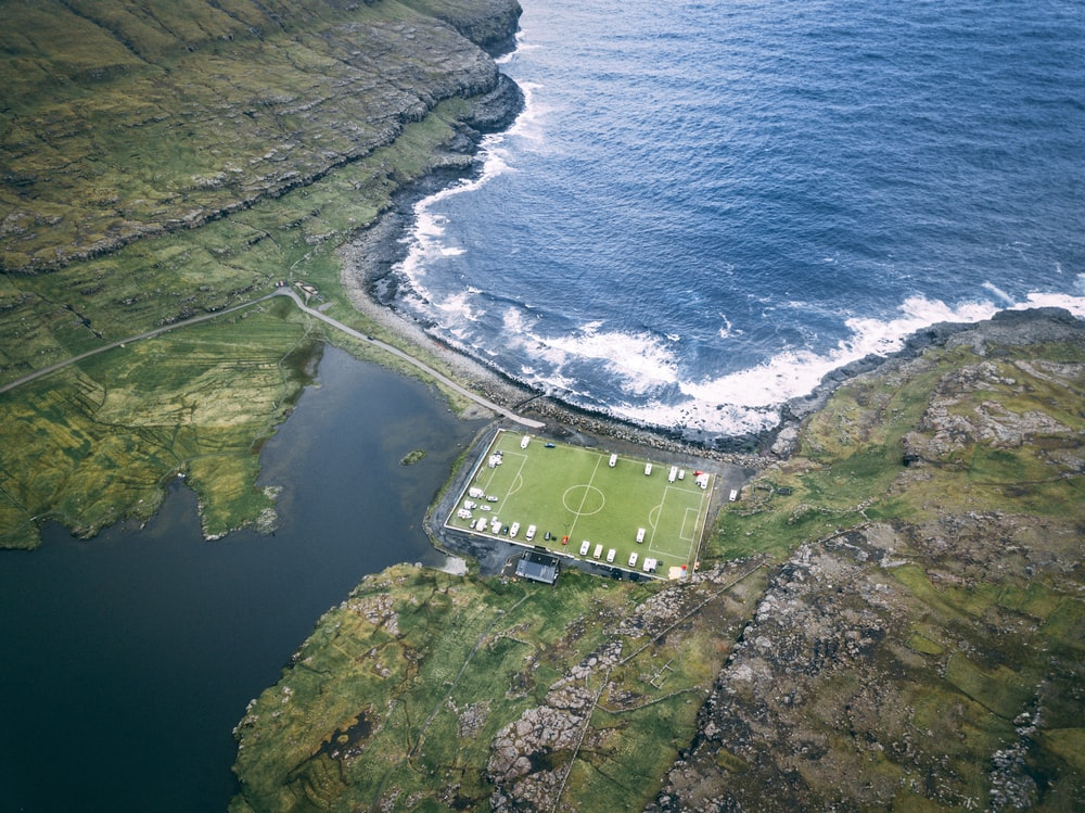 aerial photo of soccer field near body of water during daytime