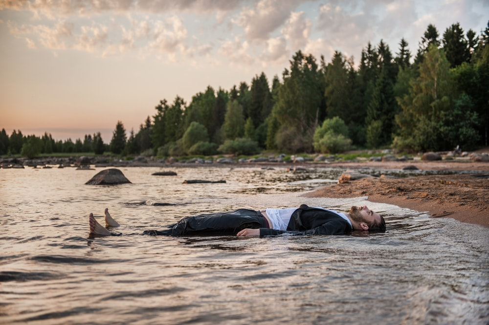 person lies in body of water