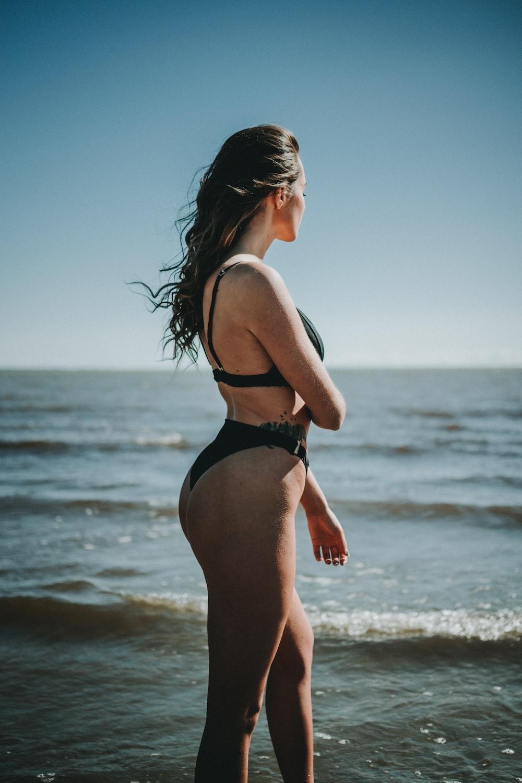 woman in bikini standing near shore