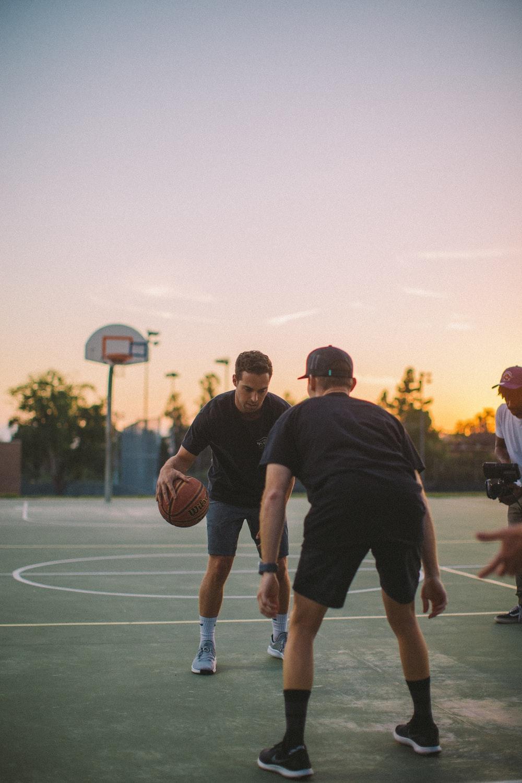 two guy playing basketball during daytime