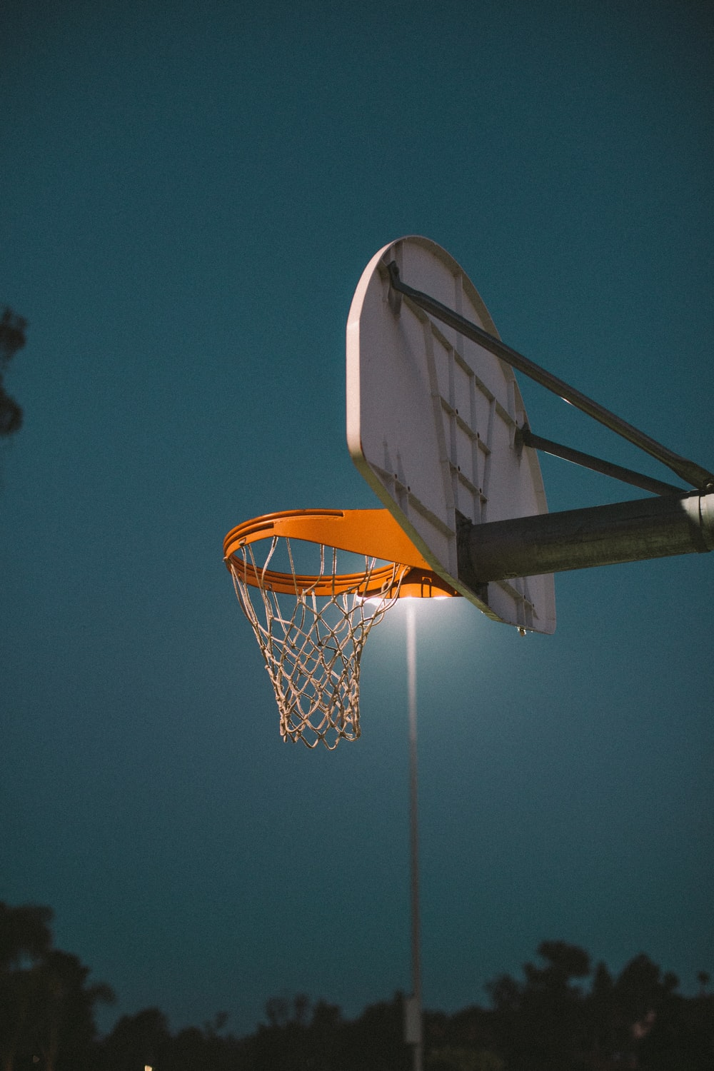 shallow focus photo of white and orange basketball hoop