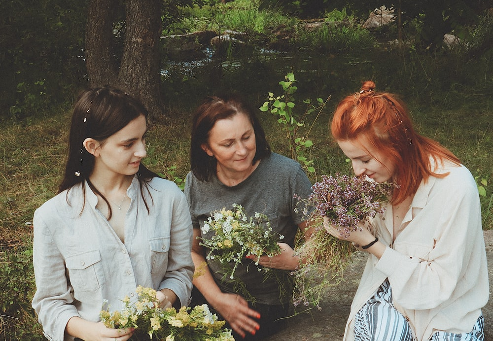 three women holding bouquet of flowers while one of them sniffing the flowers