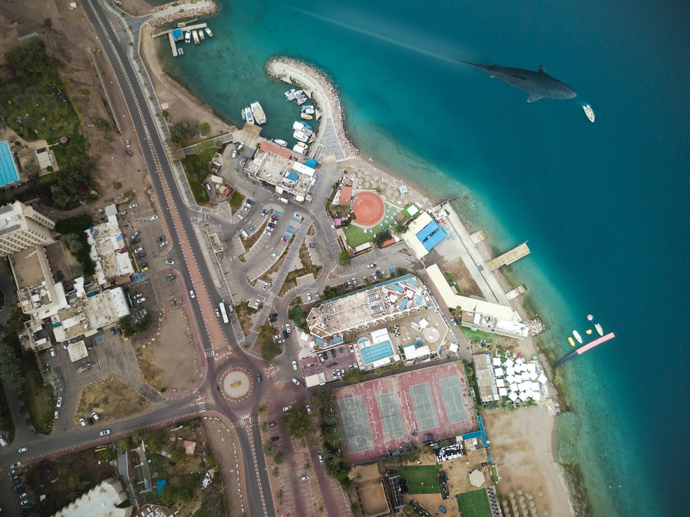 aerial photography of buildings beside blue beach