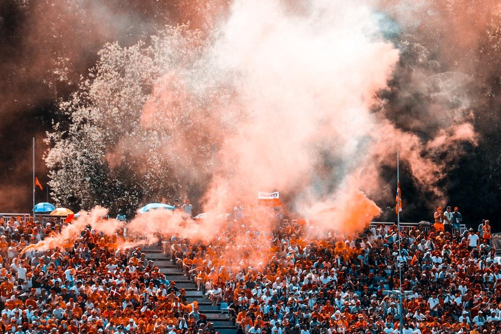 aerial photo of people sitting on stadium with orange smokes above them