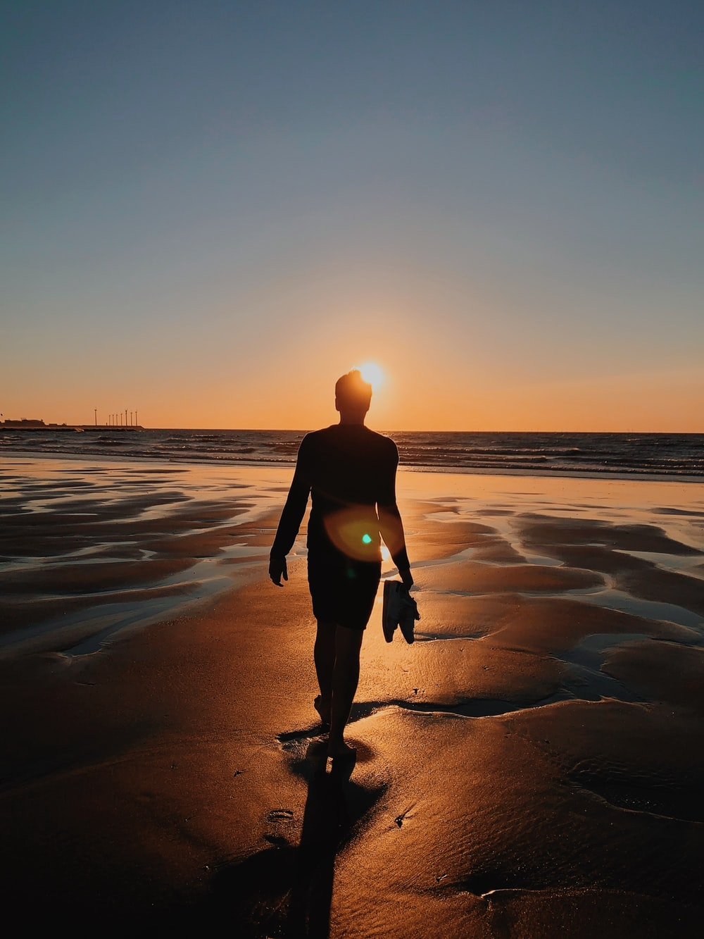 silhouette of person standing on shore