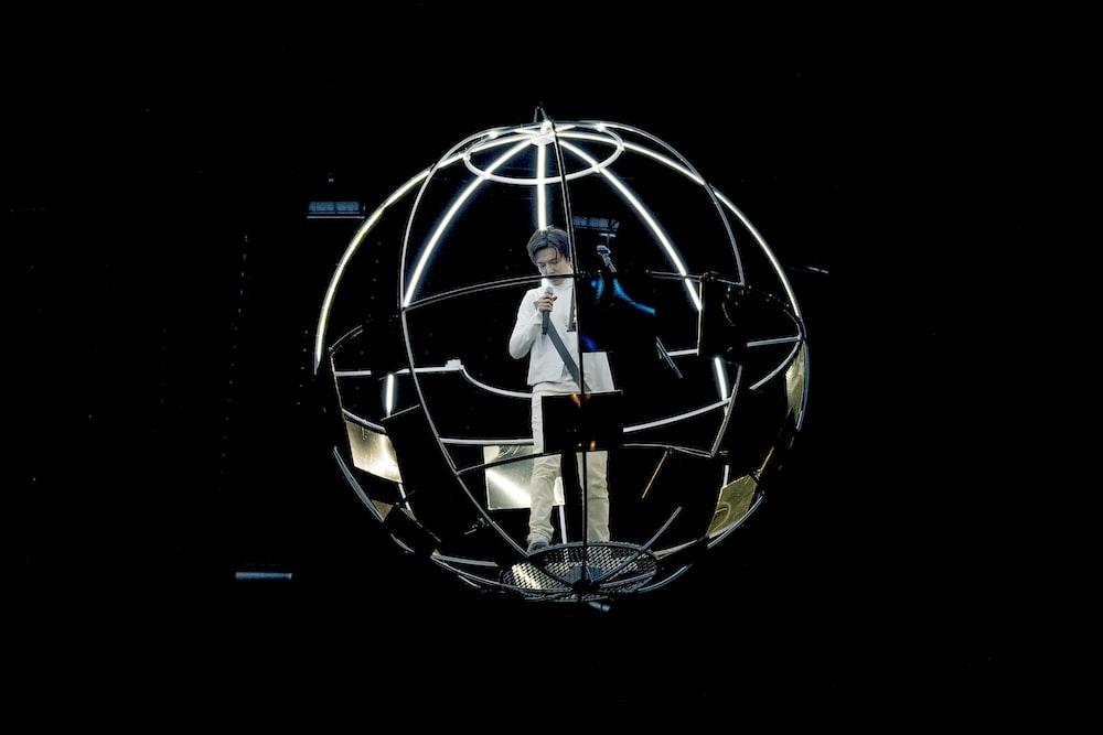 man standing near globe frame