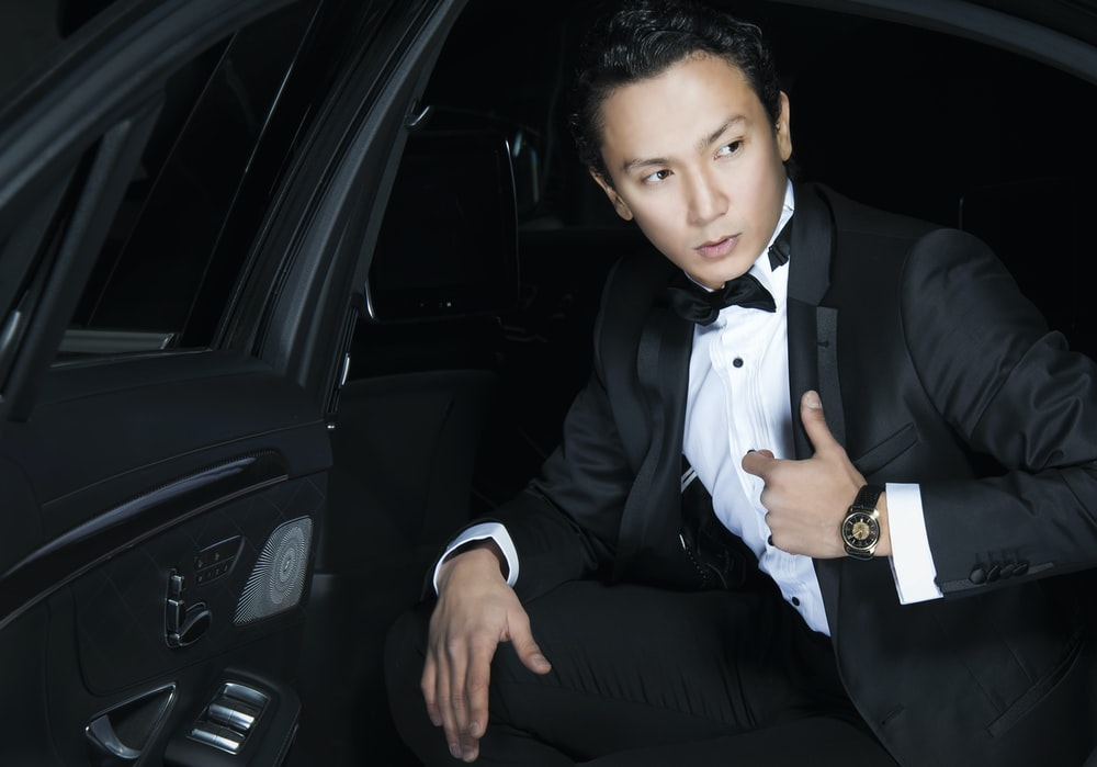 man in black blazer sits inside the car