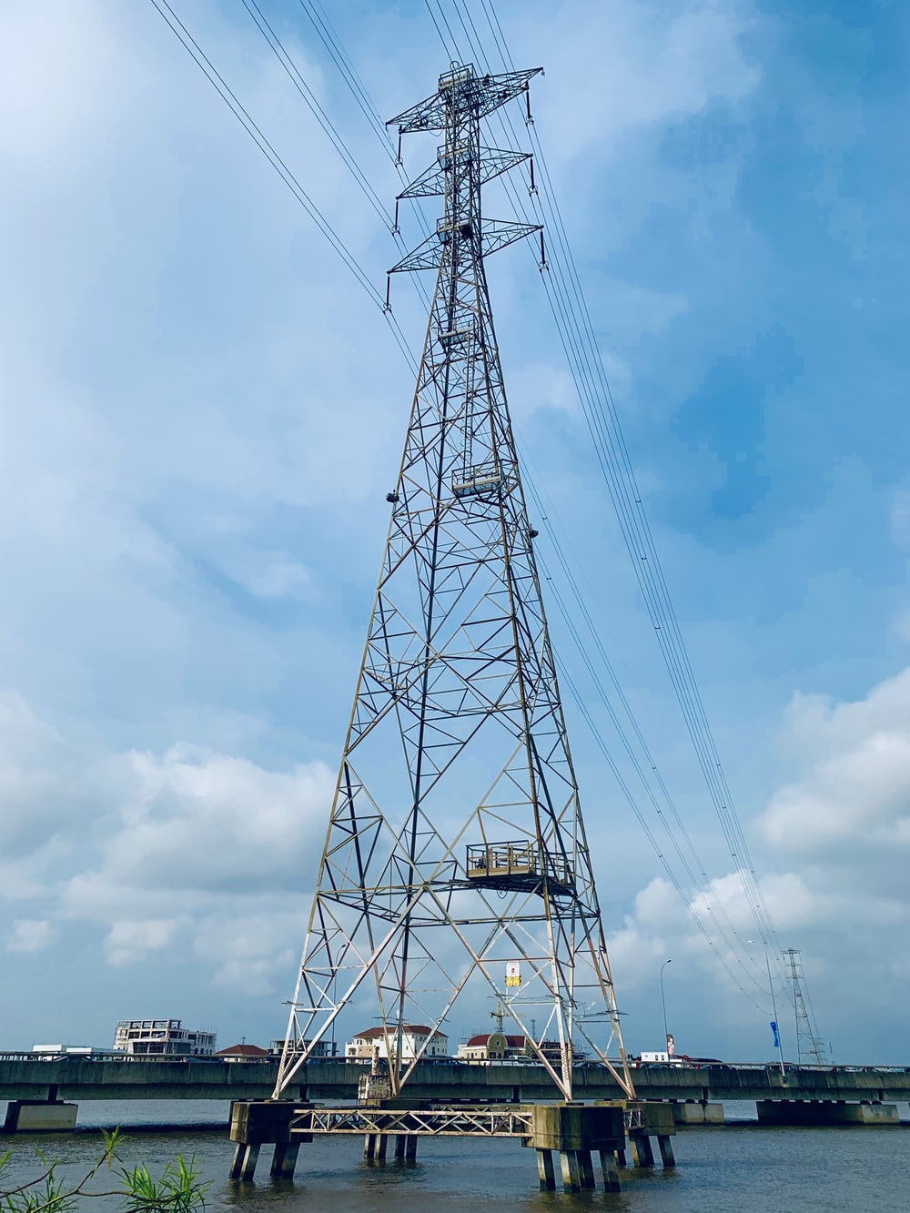 gray metal transmission tower in body of water