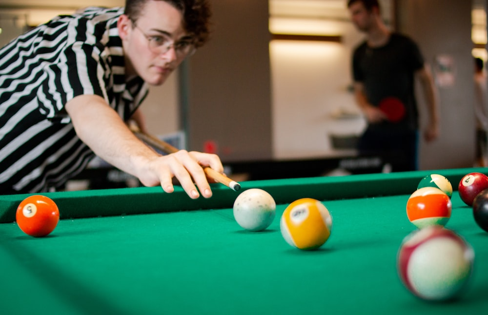 man in black and white striped playing billiard