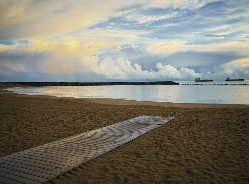 brown wooden dock on brown sand