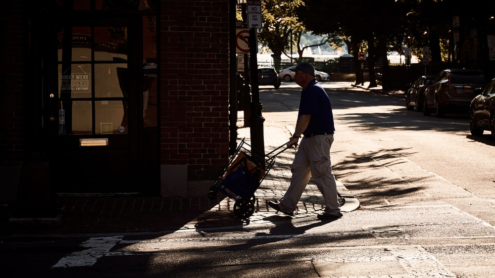 man pushing a cart along the street