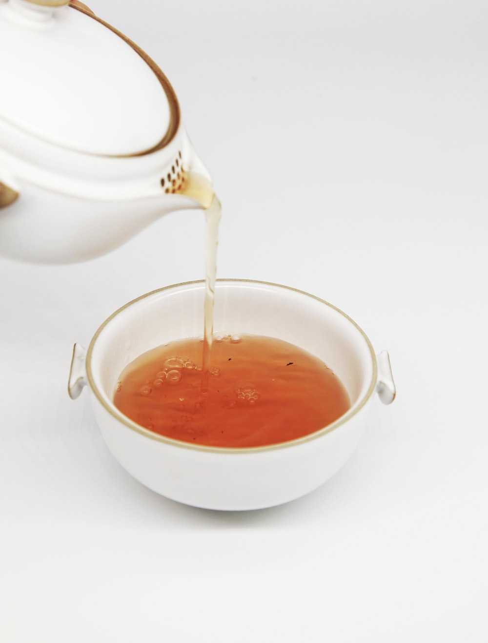 tea pours into white teacup
