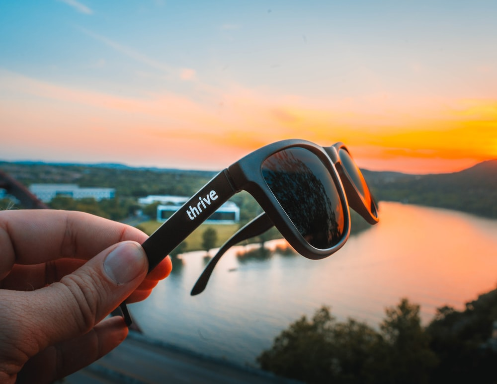 person holding black Thrive wayfarer sunglasses