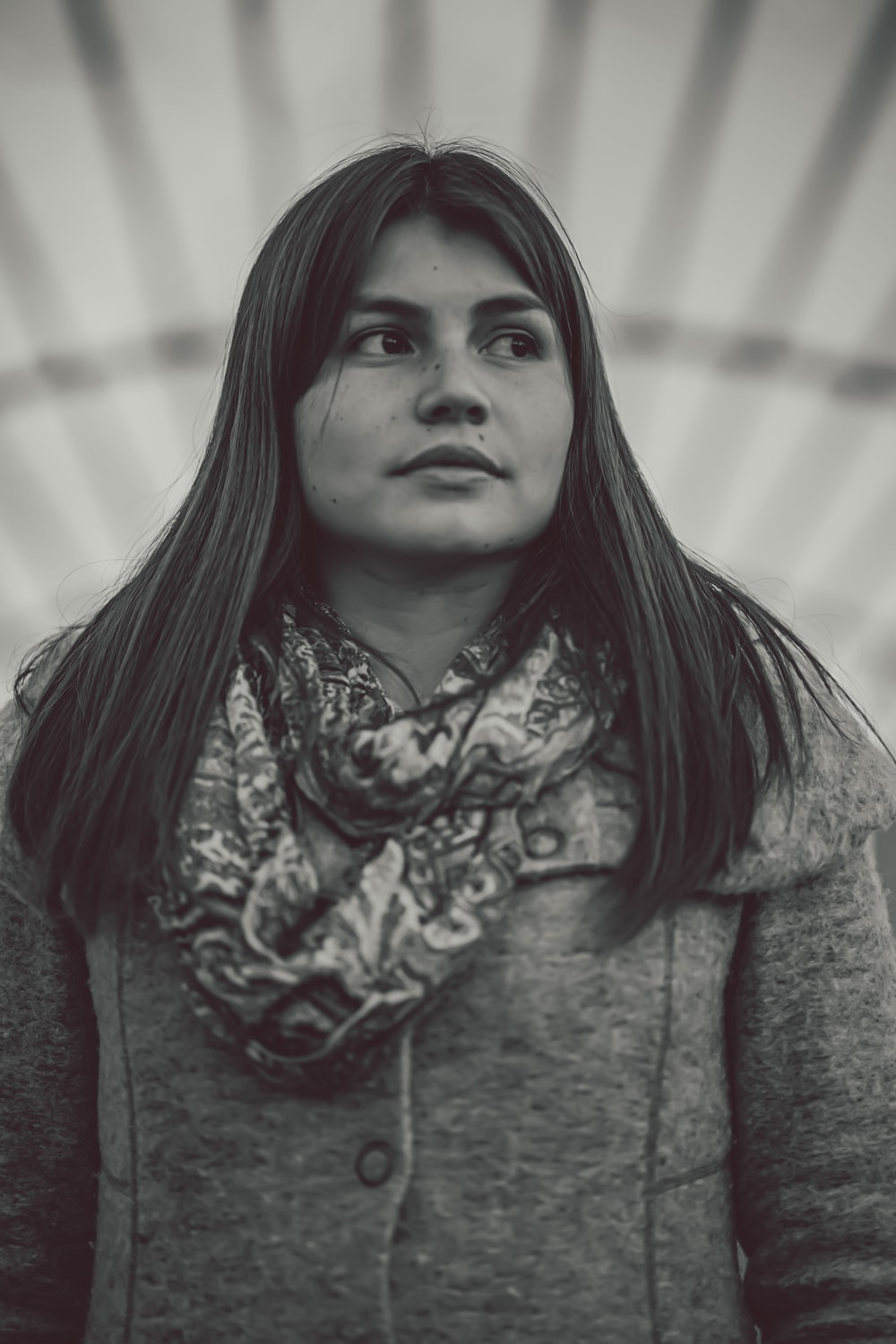 grayscale photo of woman wearing coat and scarf