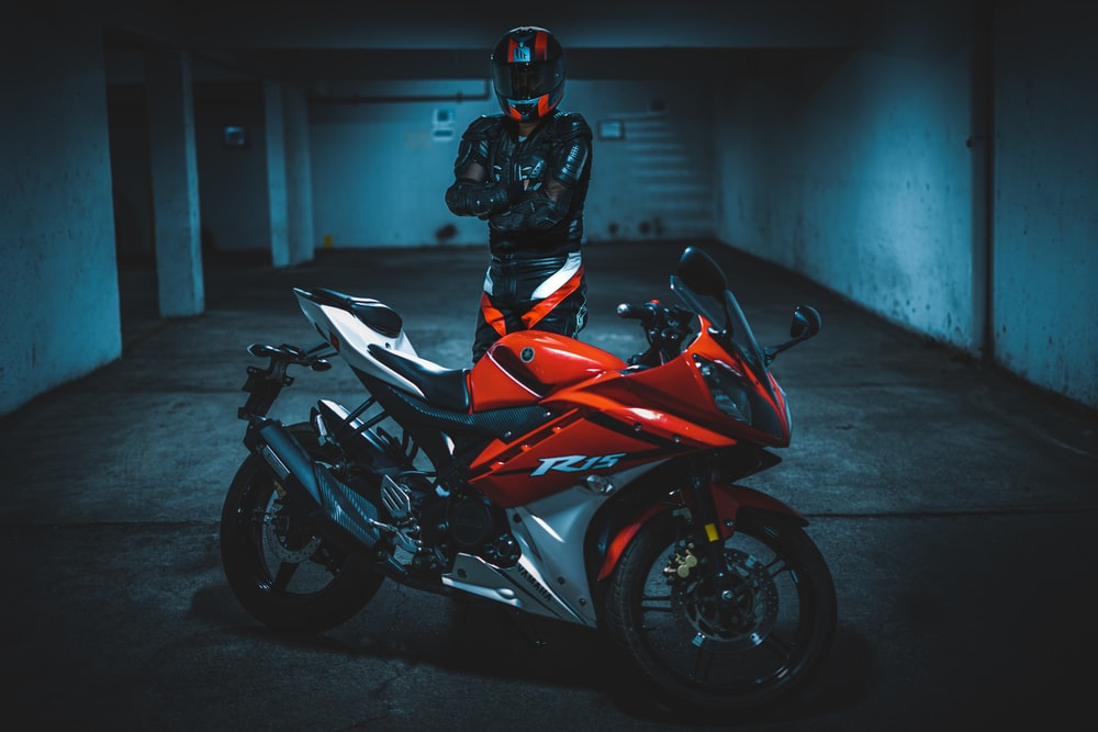 person standing in front of black and red sports bike