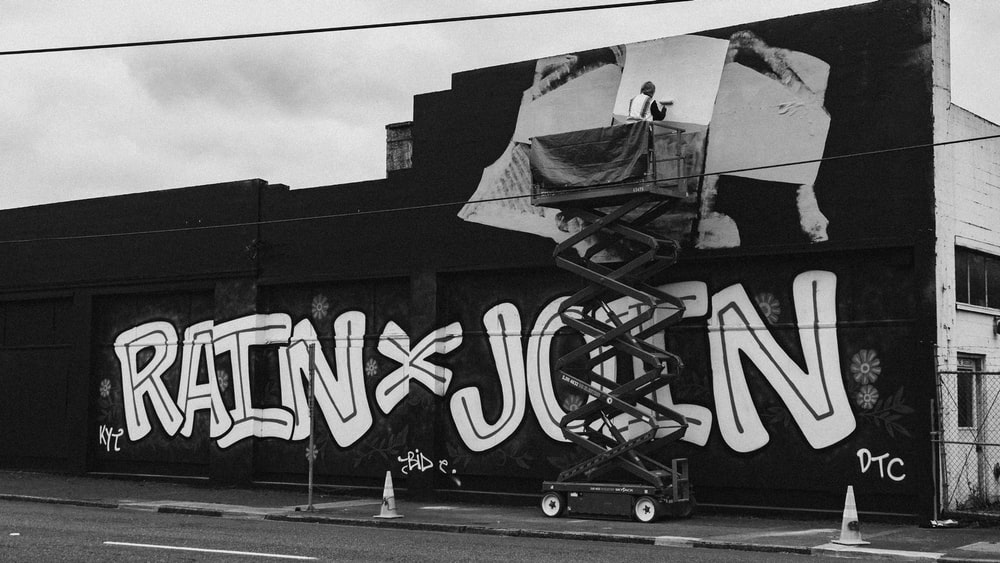 grayscale photography of wall with graffiti paint
