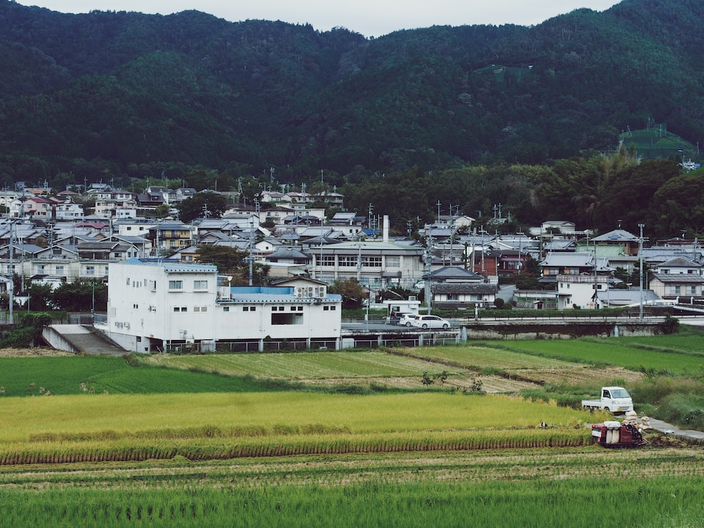 landscape photography of buildings beside mountain ange