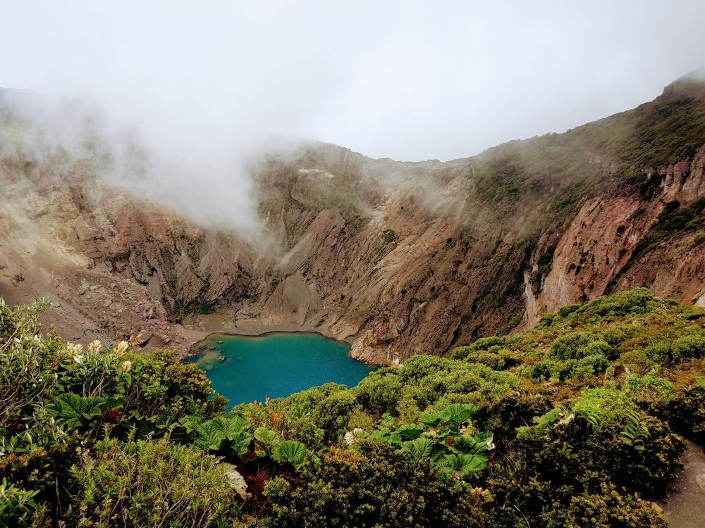 lake at the center of mountain at daytime