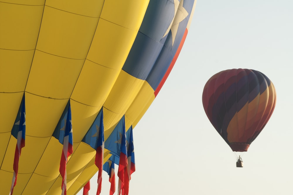 two yellow hot air balloons on sky