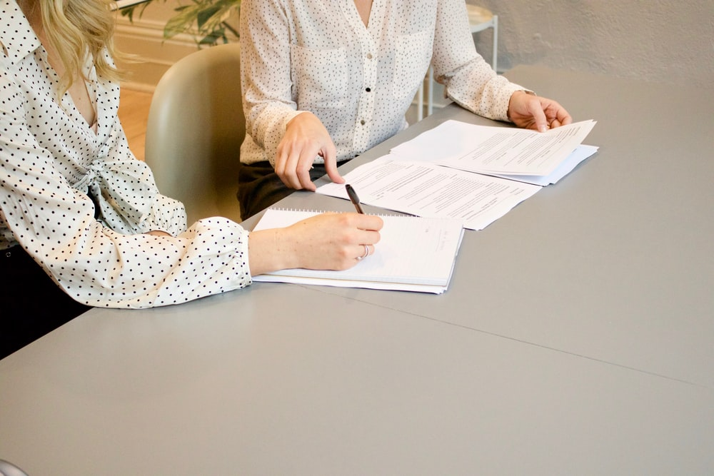 woman signing on white printer paper beside woman about to touch the documents