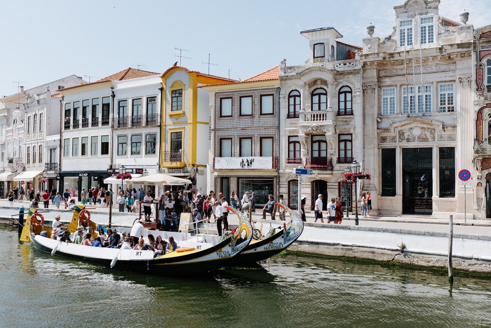 people in boat in front of buildings