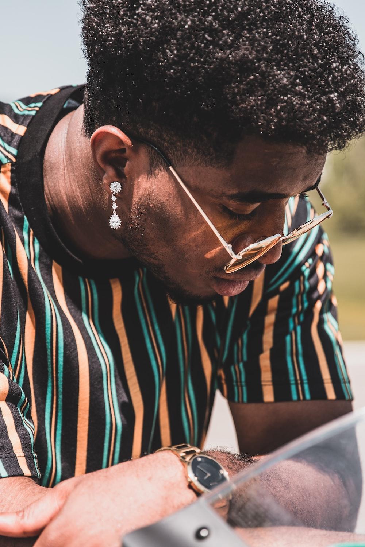 man in black, orange, and blue striped shirt