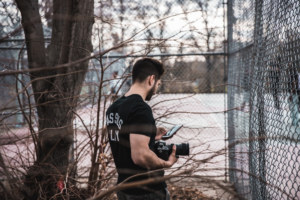 man using phone and holding camera standing in the corner fence