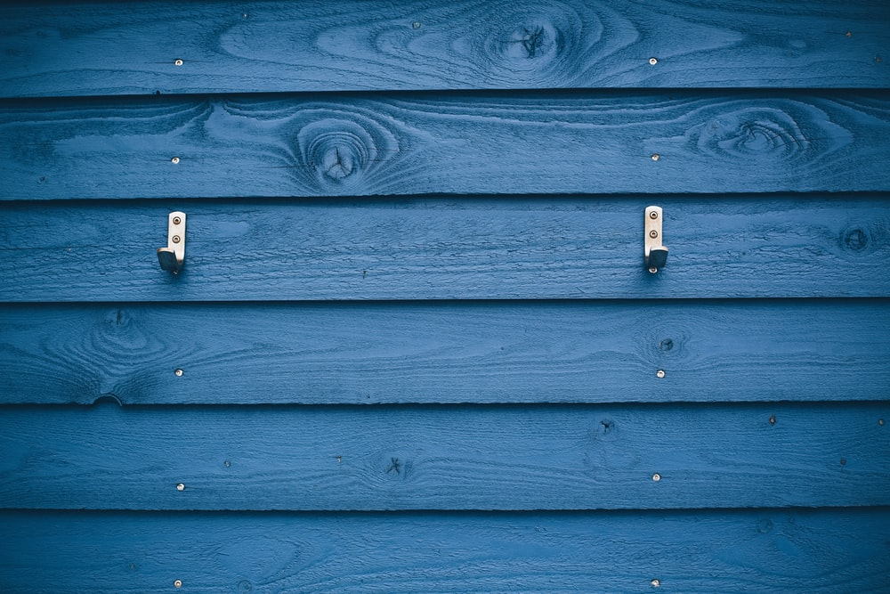 grey metal hook on blue wood plank