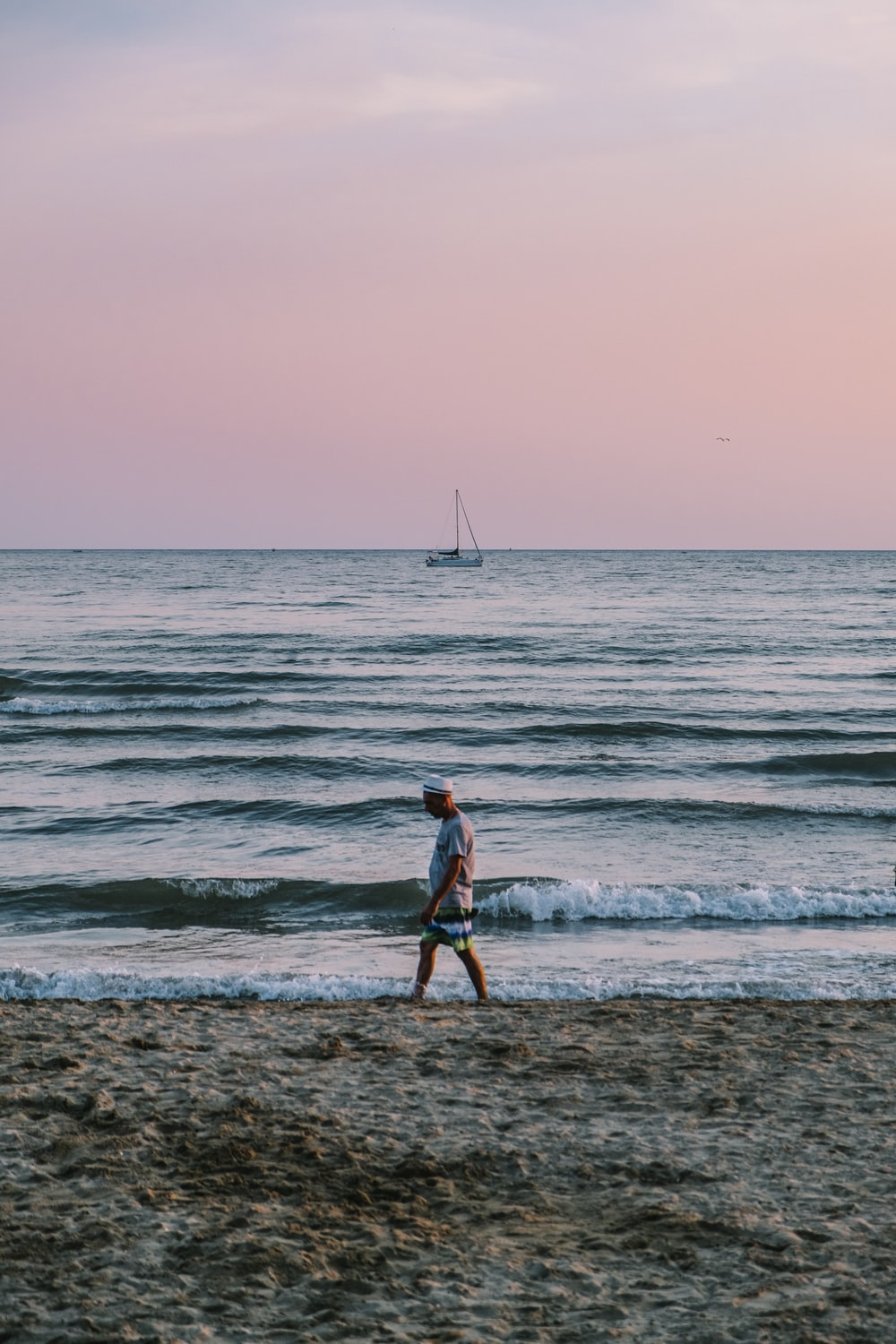 person standing beside body of water during golden hour