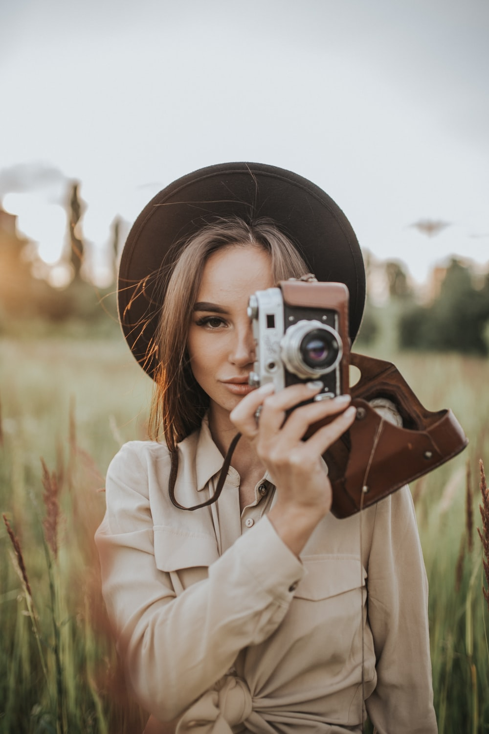 woman holding camera in field during daytime