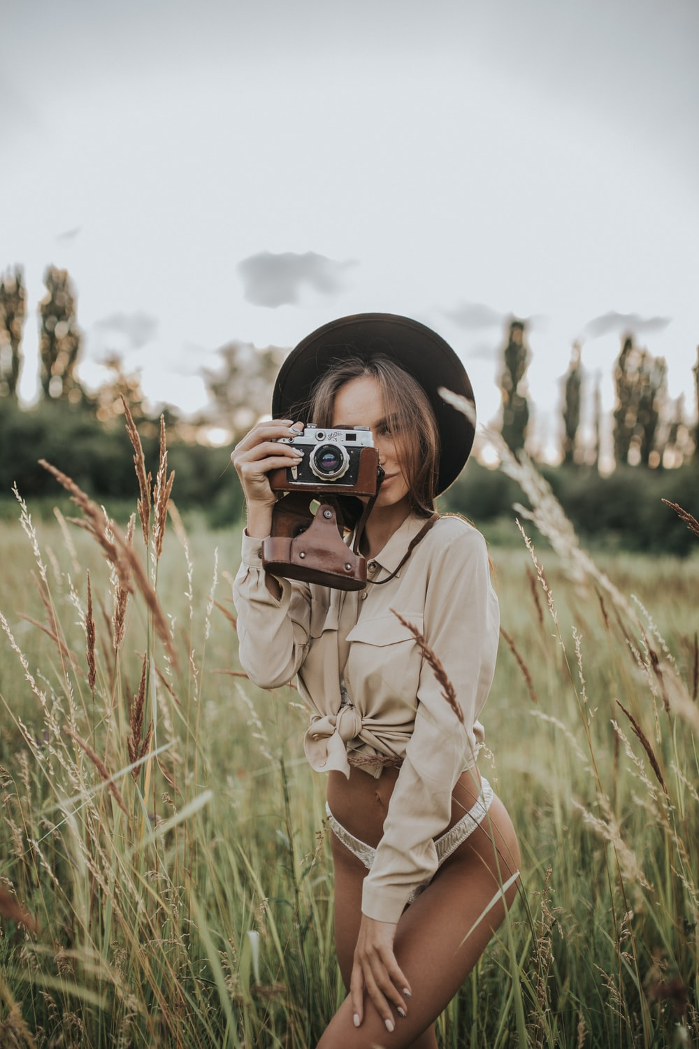 woman wearing white pantie holding gray and brown camera