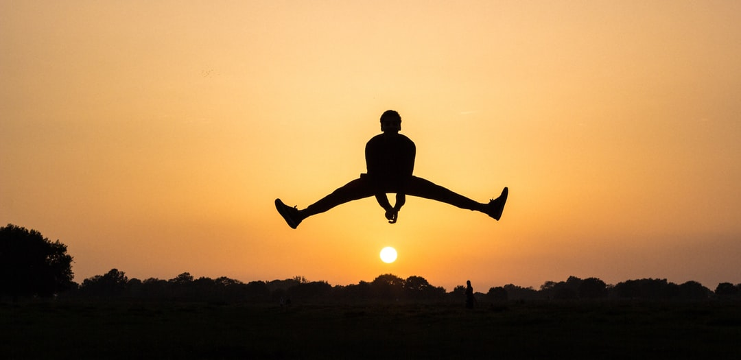 A silhouette jumping above the sun