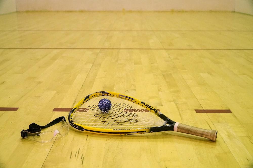 black ball beside yellow and black racquetball racket