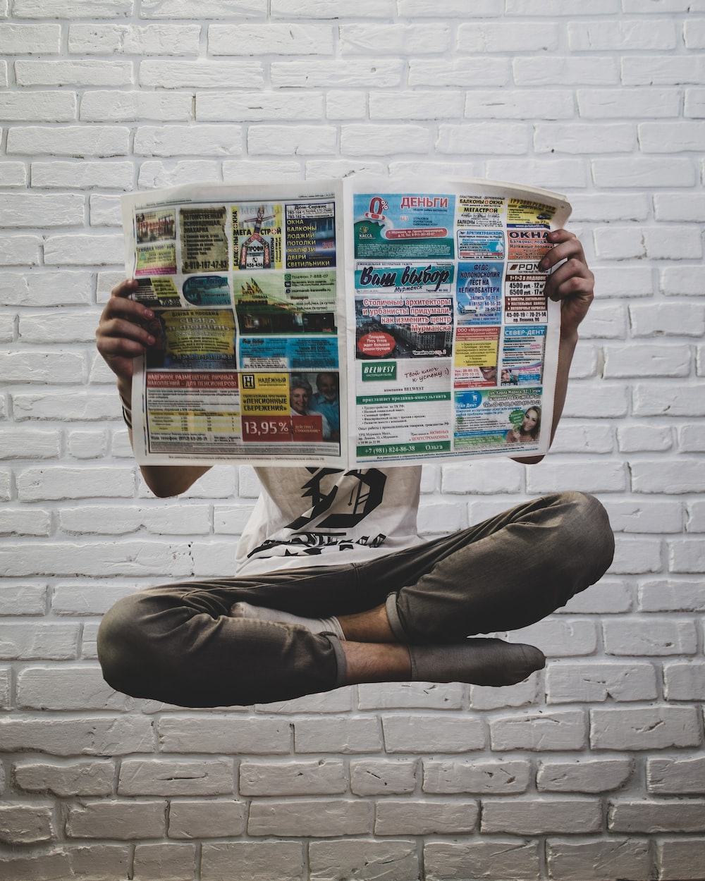 person holding newspaper article
