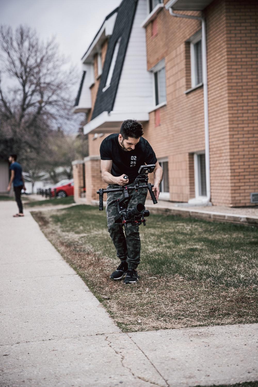 man using drone standing in green field