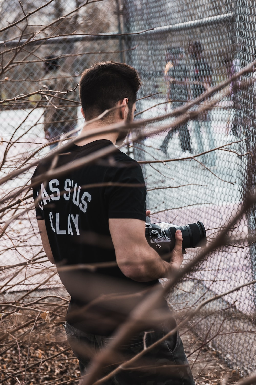 man holding camera standing near fence