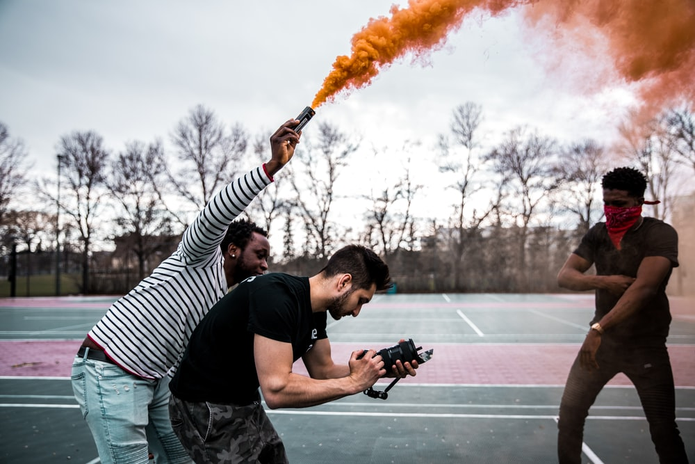 man holding can with orange smoke standing beside man holding camera