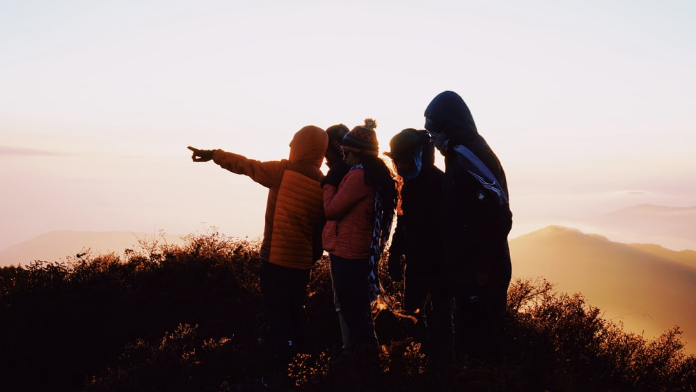 group of people standing on hill during sunrise