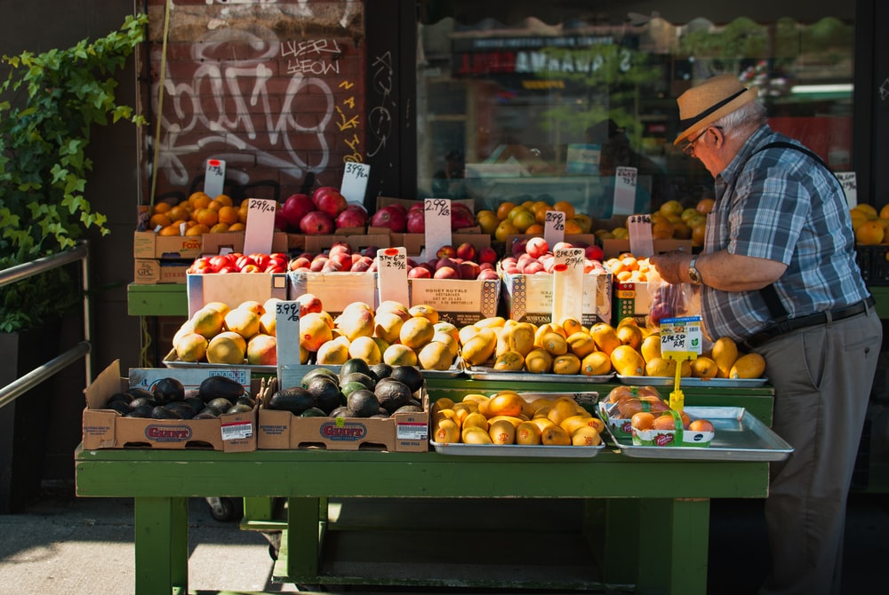 man picking fruit from a fruit stand