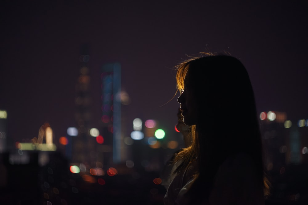 silhouette of woman standing near building