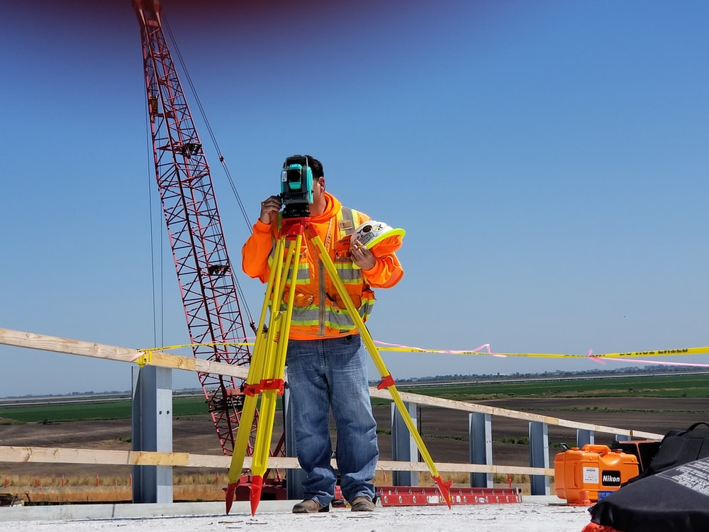 man standing and using measuring level on road